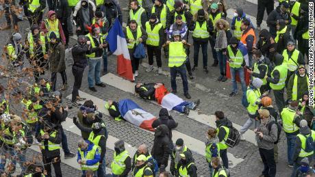 I manifestanti avvolti in bandiere francesi si trovano sul terreno vicino la polizia antisommossa sugli Champs Elysees 8 dicembre 2018.