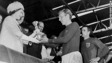 The Queen hands the Jules Rimet Trophy to Bobby Moore after England win the 1966 World Cup final.