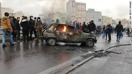 Iranian protesters gather around a burning car during a demonstration against an increase in gasoline prices in the capital Tehran on November 16, 2019.