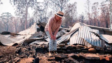 Bushfire survivor Melinda Plesman examines the remains of her destroyed property in Nymboida, NSW.