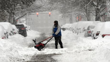 Mike Coutsonikas tries to clear sidewalks and cars of snow Monday in Albany, New York.