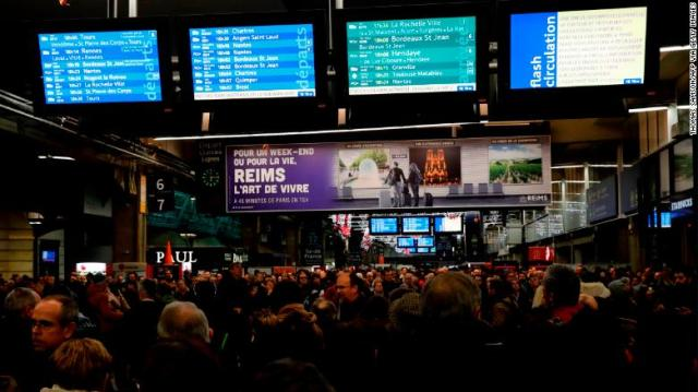 Commuters walk inside Montparnasse train station in Paris on December 4, 2019, on the eve of a national strike over pension reforms.