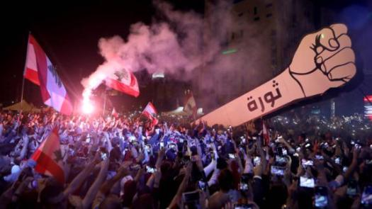 Demonstrators raise a giant fist sign that bears the Arabic word for