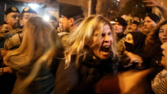 Anti-government protesters scuffle with riot police on December 4 in Beirut.