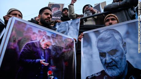 Protesters shout slogans against the United States and Israel as they hold posters with the image of top Iranian commander Qasem Soleimani, who was killed in a US airstrike in Iraq.