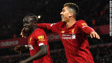Mane (left) celebrates scoring against Sheffield United with teammate Roberto Firmino.