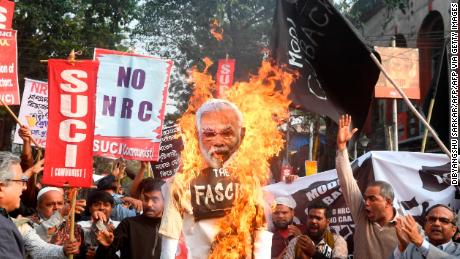 Activists of the Social Unity Center of India (SUCI) burn an effigy of India's Prime Minister Narendra Modi as they participate in a protest against India's new citizenship law, in Kolkata on January 11, 2020.