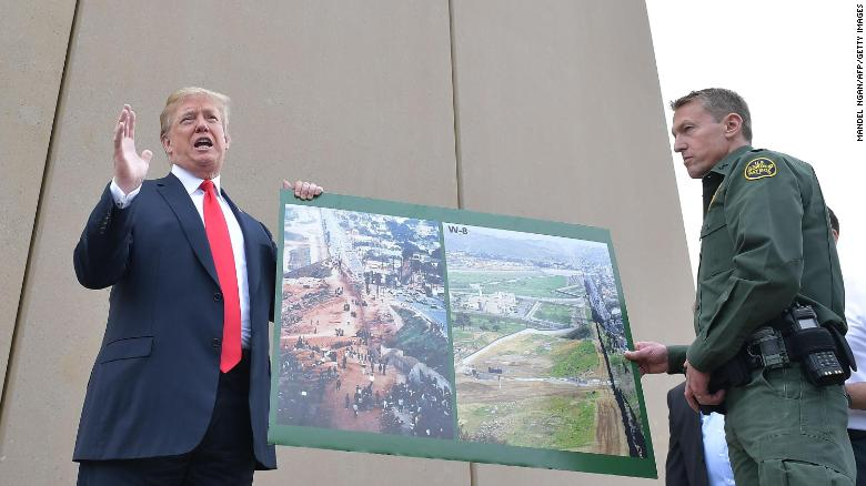 US President Donald Trump holds up a poster of before and after photos of a segment of the  border wall prototypes with Chief Patrol Agent Rodney S. Scott in San Diego, California on March 13, 2018.