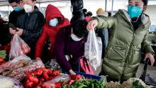 Residents wear masks to buy vegetables at a market in Wuhan on January 23, 2020.