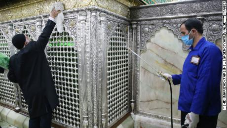 Iranian sanitary workers disinfect Qom's Masumeh shrine on February 25, 2020 to prevent the spread of the coronavirus which reached Iran.