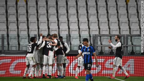 Juventus players celebrate after scoring against Inter Milan in an empty stadium.