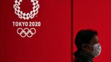 A woman in a face mask walks past a display showing the Tokyo 2020 Olympic Games logo in Tokyo on March 24, 2020.