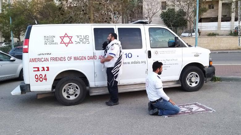 ユダヤ人救急救命士アヴラハムミンツはエルサレムに向かい、祈りのショールは肩から垂れ下がっています。 イスラム教の救急救命士Zoher Abu Jamaはメッカに向かってひざまずき、彼の祈りの敷物は彼の前に広げられた。
