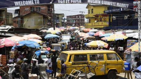 People walk in a crowded market in defiance to a social spacing order, to make last minute shopping ahead of a curfew, at the Mushin Market in Lagos.