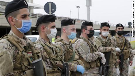 Lebanese soldiers, wearing protective equipment, stand guard at Beirut international airport on April 5, ahead of the arrival of returning nationals.