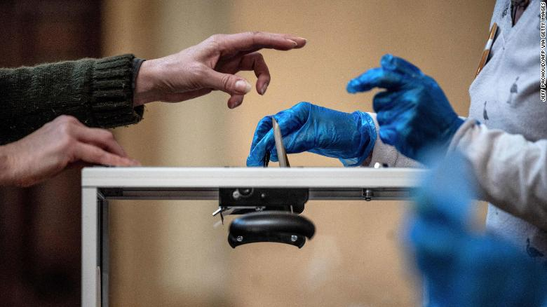 A voter casts their ballot in front of an official wearing plastic gloves in a polling station in Lyon on March 15.