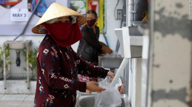 A woman fills a plastic bag with rice from a 24/7 automatic rice dispensing machine in Ho Chi Minh City, Vietnam, on April 11, 2020.