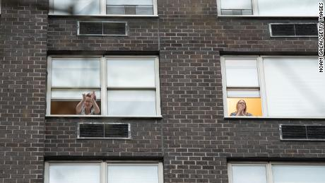 People applaud from their windows to show gratitude to medical staff and essential workers on the frontlines of the coronavirus pandemic on April 3, 2020 in New York City.