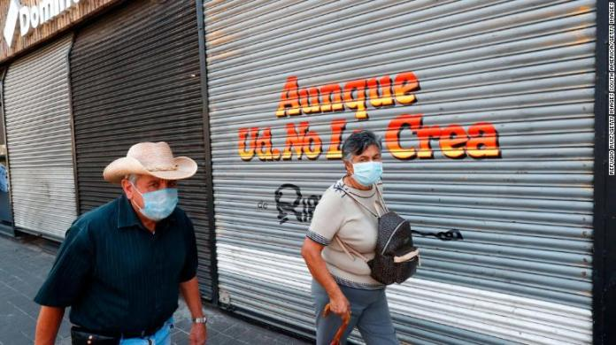 People walk by a closed store during the pandemic in Guadalajara City,  Mexico.