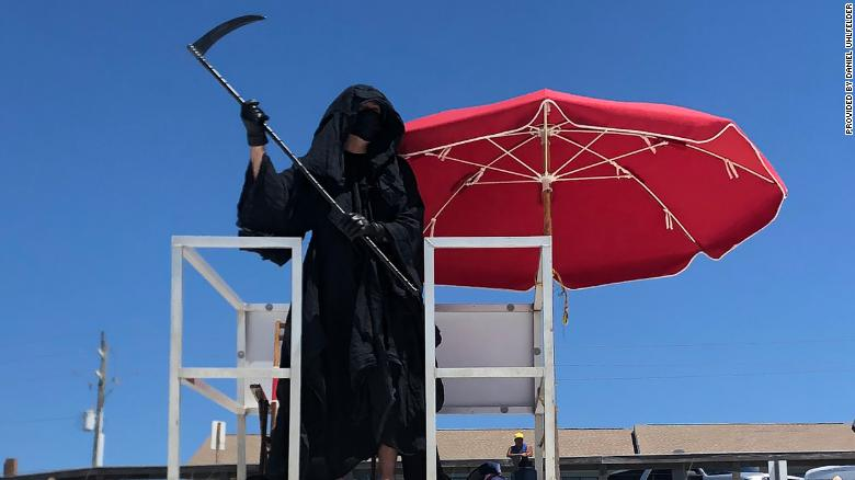 Daniel Uhlfelder, a Florida lawyer, is haunting Florida beaches dressed as the Grim Reaper to protest their reopening, which he believes is premature.