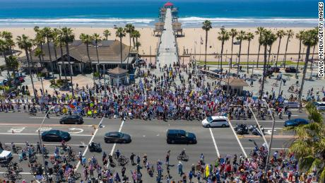 An aerial view shows a crowd of protesters calling for the reopening of businesses and beaches as the coronavirus pandemic continues to paralyze the economy in Huntington Beach, California on Friday.