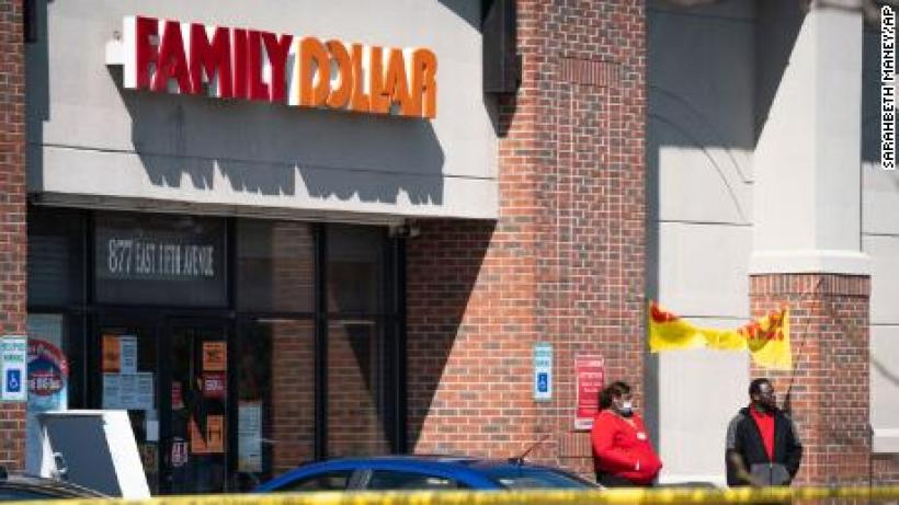 In this Friday, May 1, 2020 photo, employees stand outside the Family Dollar as police investigate a shooting that took place at the store in Flint, Mich.