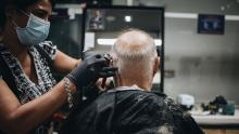 A stylist wearing a protective mask and gloves cuts a customer's hair at a barber shop in Coral Gables, Florida, U.S., on Monday, May 18, 2020. Florida Governor Ron DeSantis announced a partial re-opening order in Miami-Dade county, the two counties hardest hit by the coronavirus outbreak.