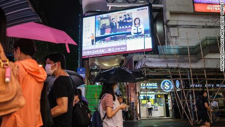 Pedestrians walk under a television screen in Hong Kong on May 21, 2020, showing a news broadcast of footage from Beijing of Chinese President Xi Jinping (C) at the Chinese People's Political Consultative Conference.