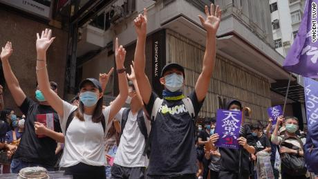 "Protesters gesture with five fingers, signifying the ""Five demands - not one less"" during a pro-democracy protest against Beijing's national security legislation in Hong Kong on May 24, 2020."