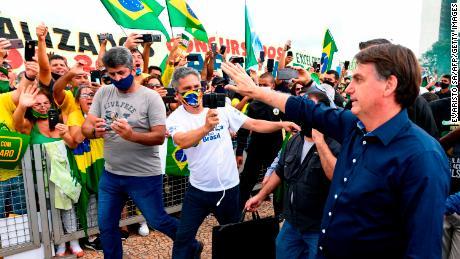 Brazil's President Jair Bolsonaro greets supporters on May 24.
