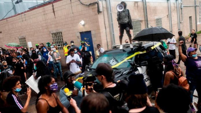 Protesters rally around a damaged police vehicle in Minneapolis on May 26.