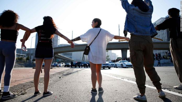 People join hands across a freeway in Los Angeles during a protest on May 27.