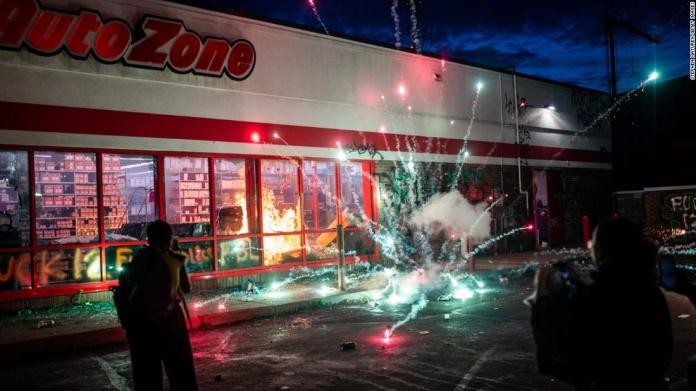 A firework explodes as a fire burns inside an Auto Zone store in Minneapolis on May 27.