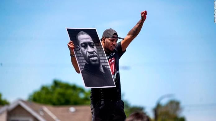 Tony L. Clark holds up a poster of George Floyd during a protest in Minneapolis on May 28.