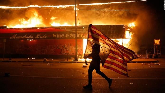 A protester carries an American flag upside down next to a burning building in Minneapolis on May 28.