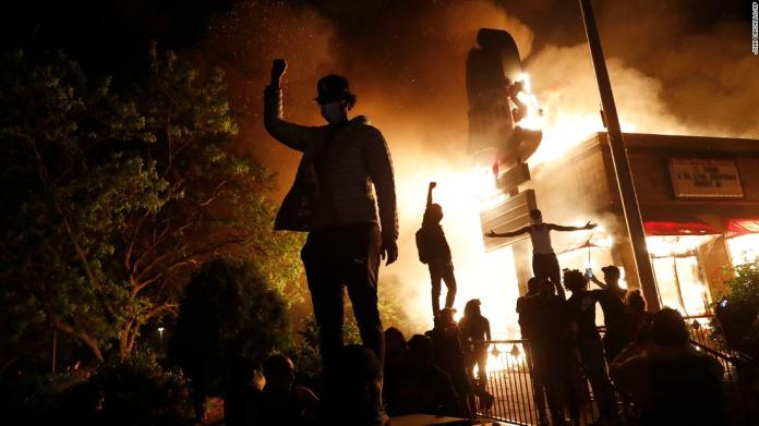 Protesters gather in front of a burning fast-food restaurant in Minneapolis on May 29.