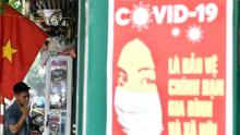 A propaganda poster on preventing the spread of the coronavirus is seen on a wall as a man smokes a cigarette along a street in Hanoi.