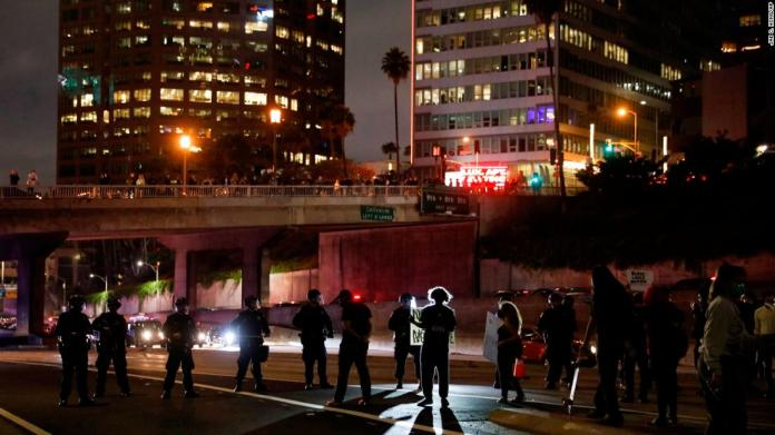 Protesters confront police officers while blocking the 110 Freeway in Los Angeles on May 29.