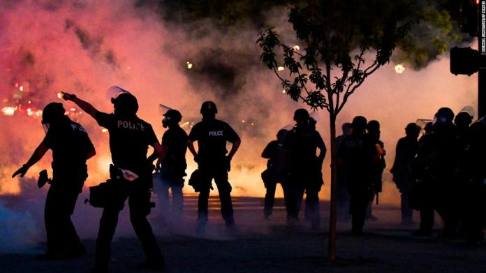 Police officers fire tear gas at protesters in Denver on May 29.