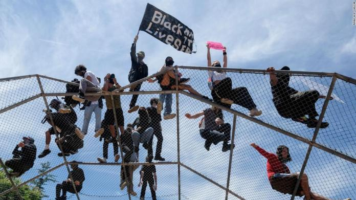 People gather on top of a baseball backstop during a protest in Los Angeles on May 30.