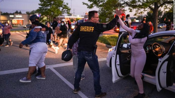 Genesee County Sheriff Chris Swanson high-fives a woman who called his name as he marches with protesters in Flint, Michigan, on May 30.
