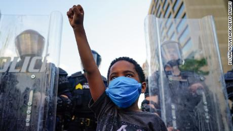 A young boy raises his fist during a demonstration on May 31 in Atlanta