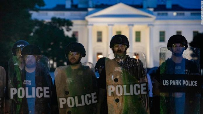 Police stand guard outside the White House as people gather to protest on May 31.