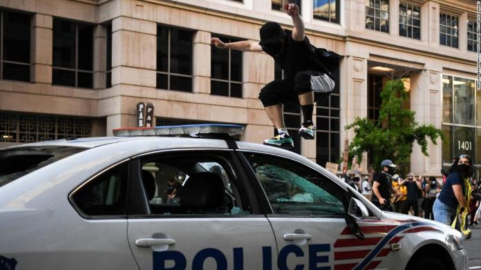 A demonstrator jumps on a police car in Washington.