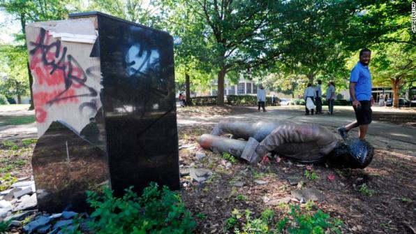 A man walks past a toppled statue of Confederate veteran Charles Linn in a Birmingham, Alabama, park, following a night of demonstrations.
