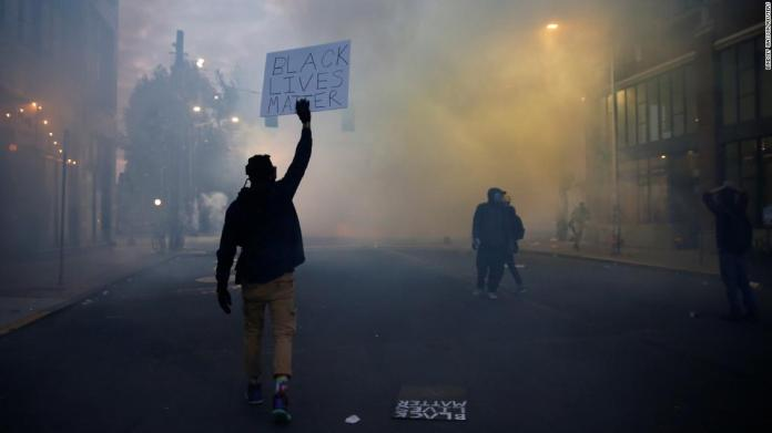 "A person holds a ""Black Lives Matter"" sign as a heavy cloud of tear gas and smoke rises in Seattle on June 1."