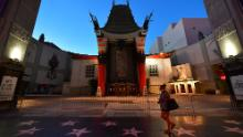A woman walks past the closed courtyard in front of the TCL Chinese theater, famous for the hand and foot prints of movie stars.