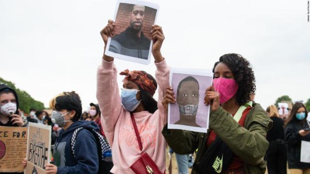 Demonstrators display pictures of George Floyd.
