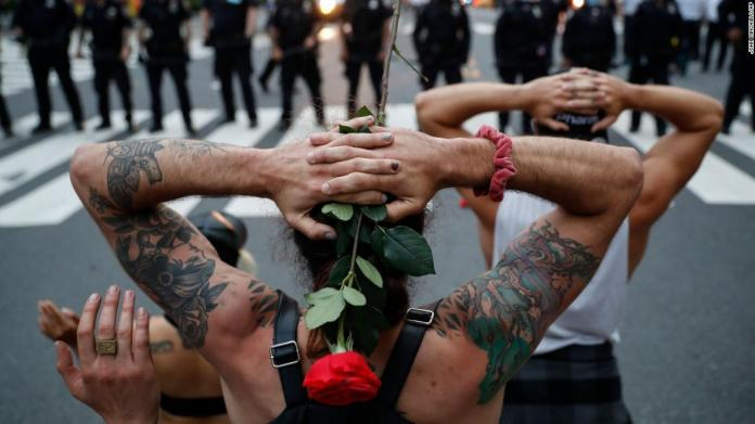 Protesters kneel in front of New York City police officers before being arrested for violating curfew on June 3.