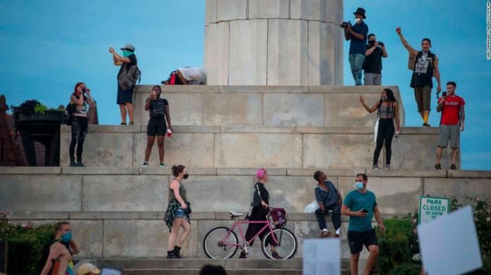 "Protesters in New Orleans gather in front of a pedestal that once displayed a statue of Confederate soldier Robert E. Lee. The Civil War-era landmark <a href=""https://edition.cnn.com/2017/05/19/us/new-orleans-confederate-monuments/index.html"" target=""_blank"">was removed in 2017</a> after a nationwide debate over Confederate symbols, which some say represent slavery and injustice and others say represent history and heritage."